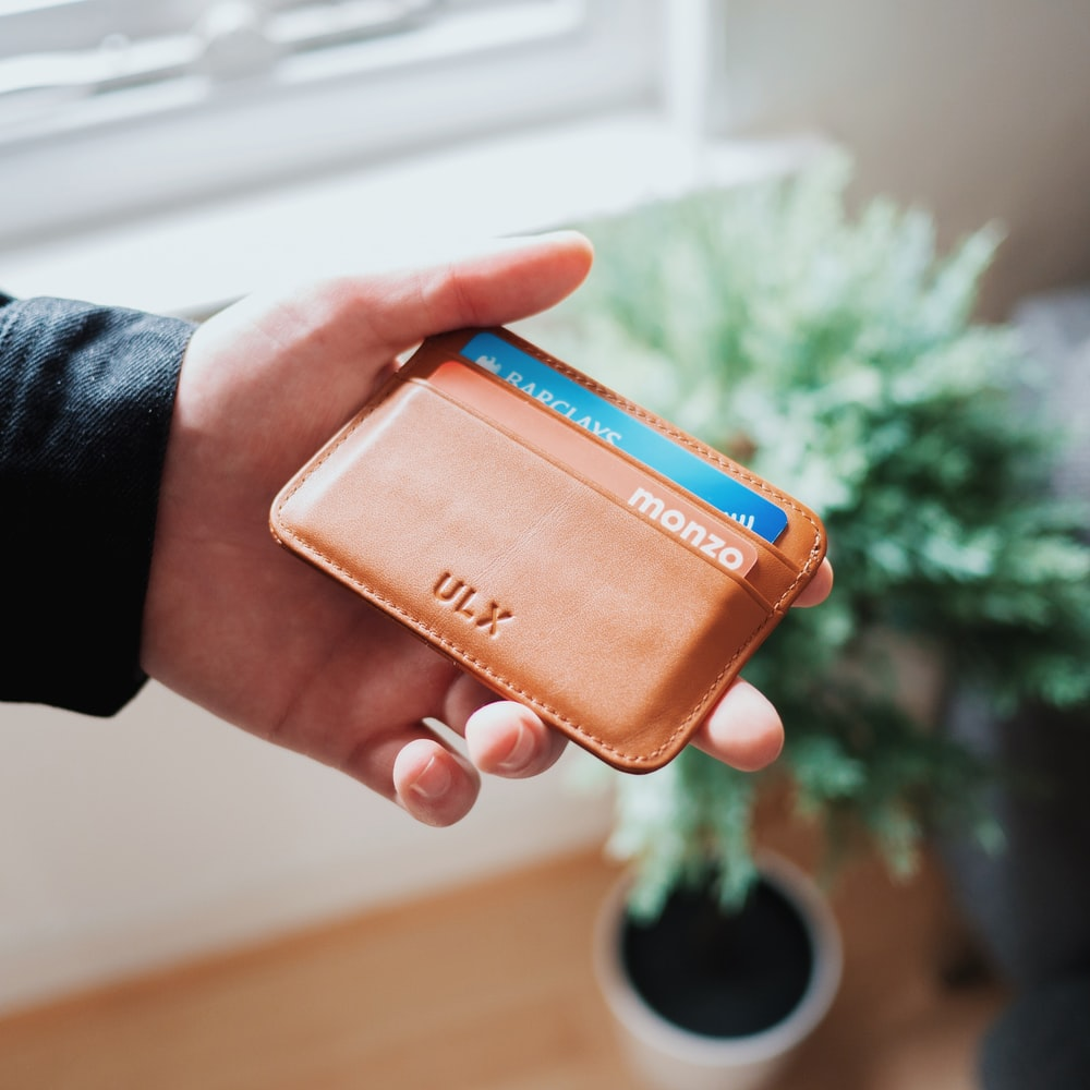 person holding brown ULX leather wallet