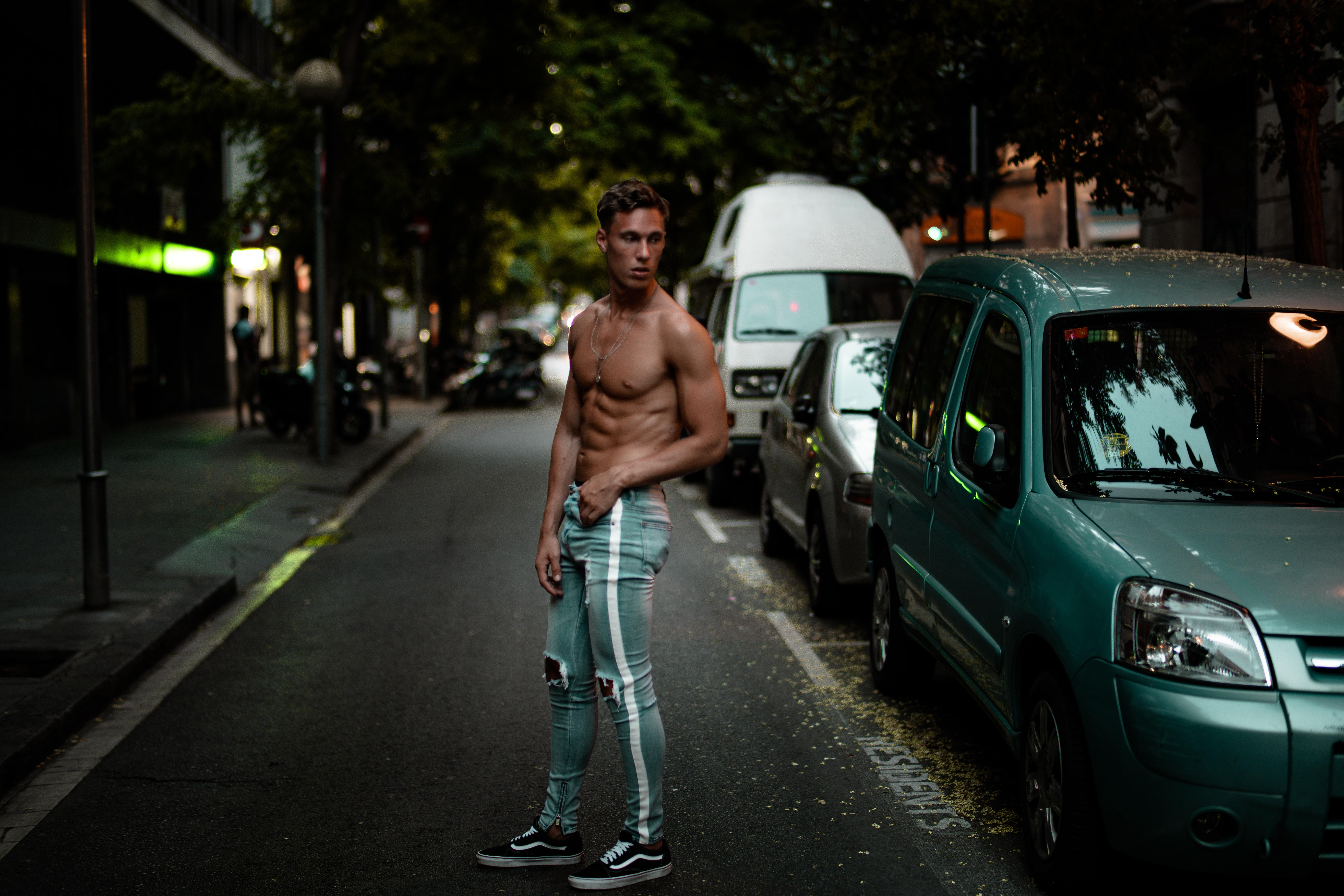 man wearing blue Amiri denim track pants standing beside green car