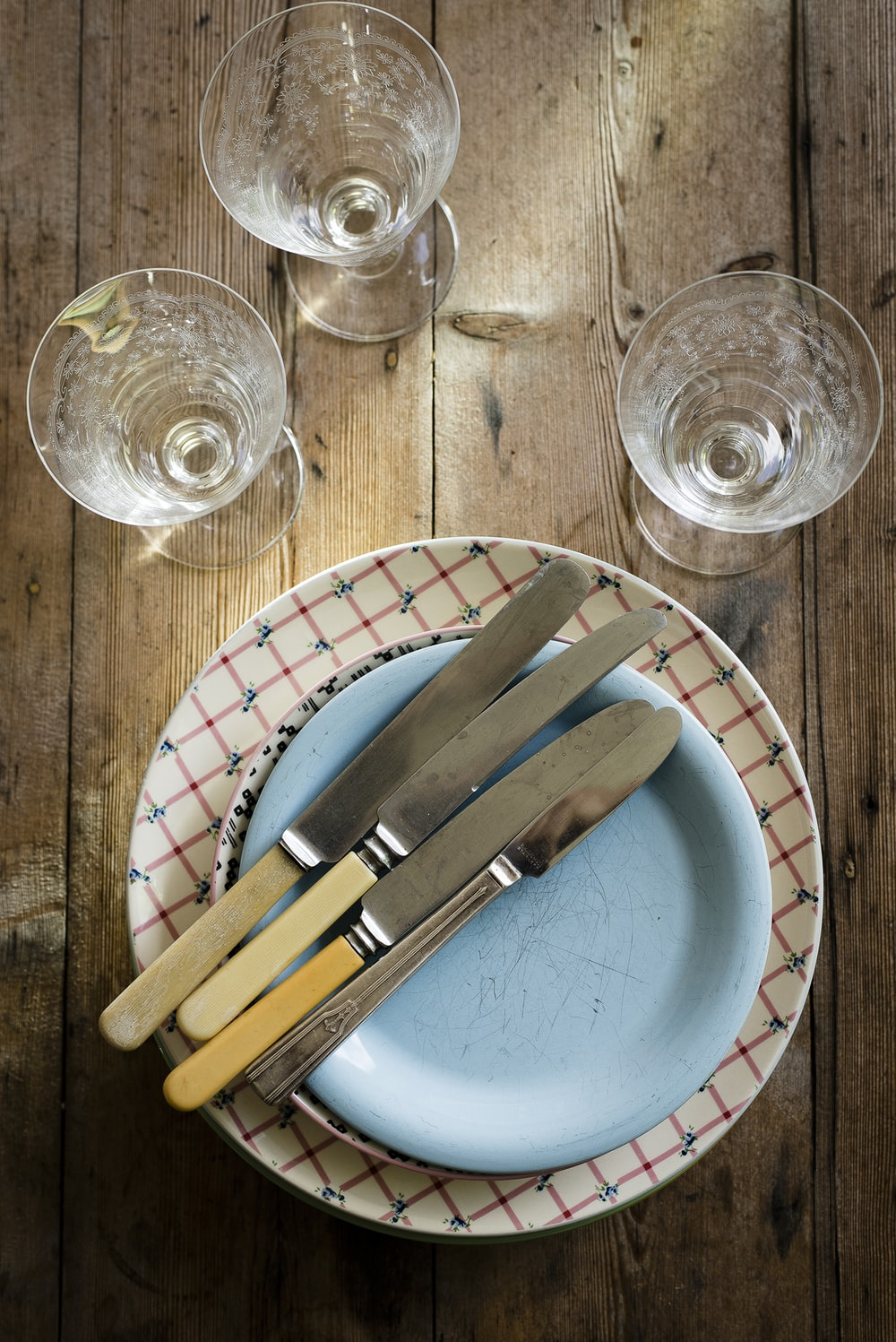 flat-lay photography of stem glasses, saucers, plate, and bread and butter knives