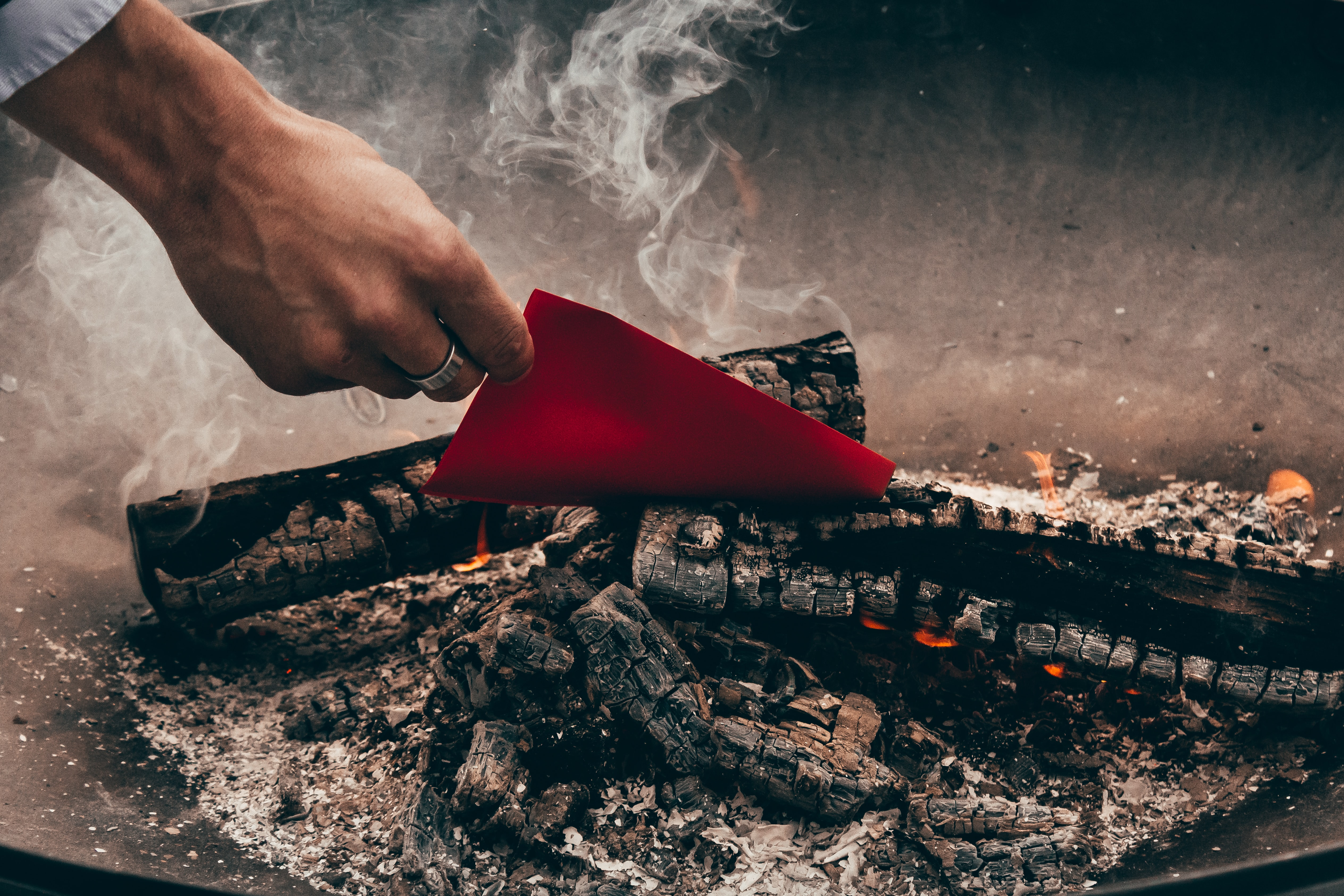 person holding red paper near charred wood