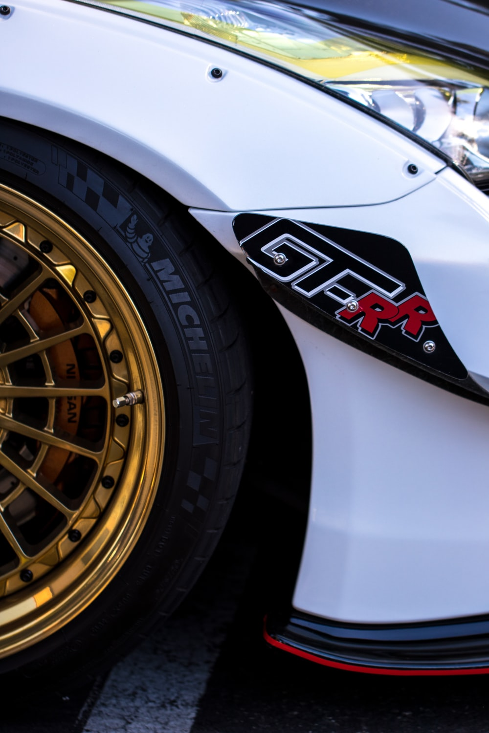 white car with gold-colored wheels and tires