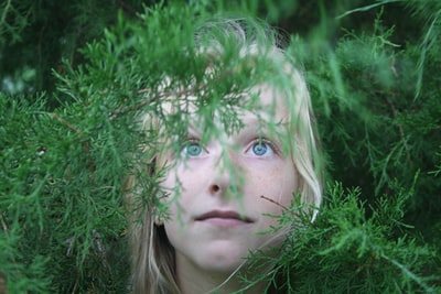 close-up photo of girl covered with plants