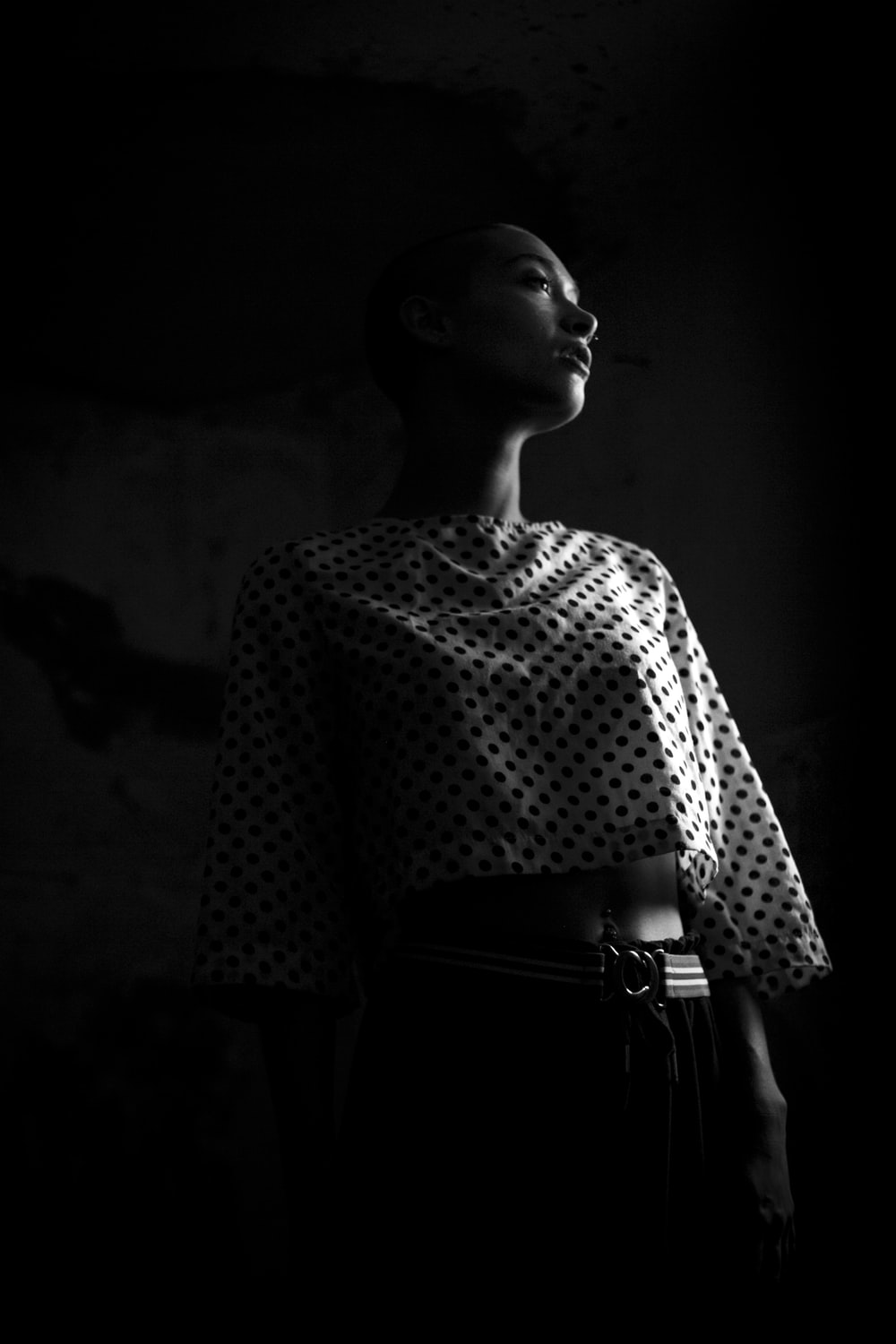 low-angle photo of woman wearing black and white polka-dot crop standing in the dark room