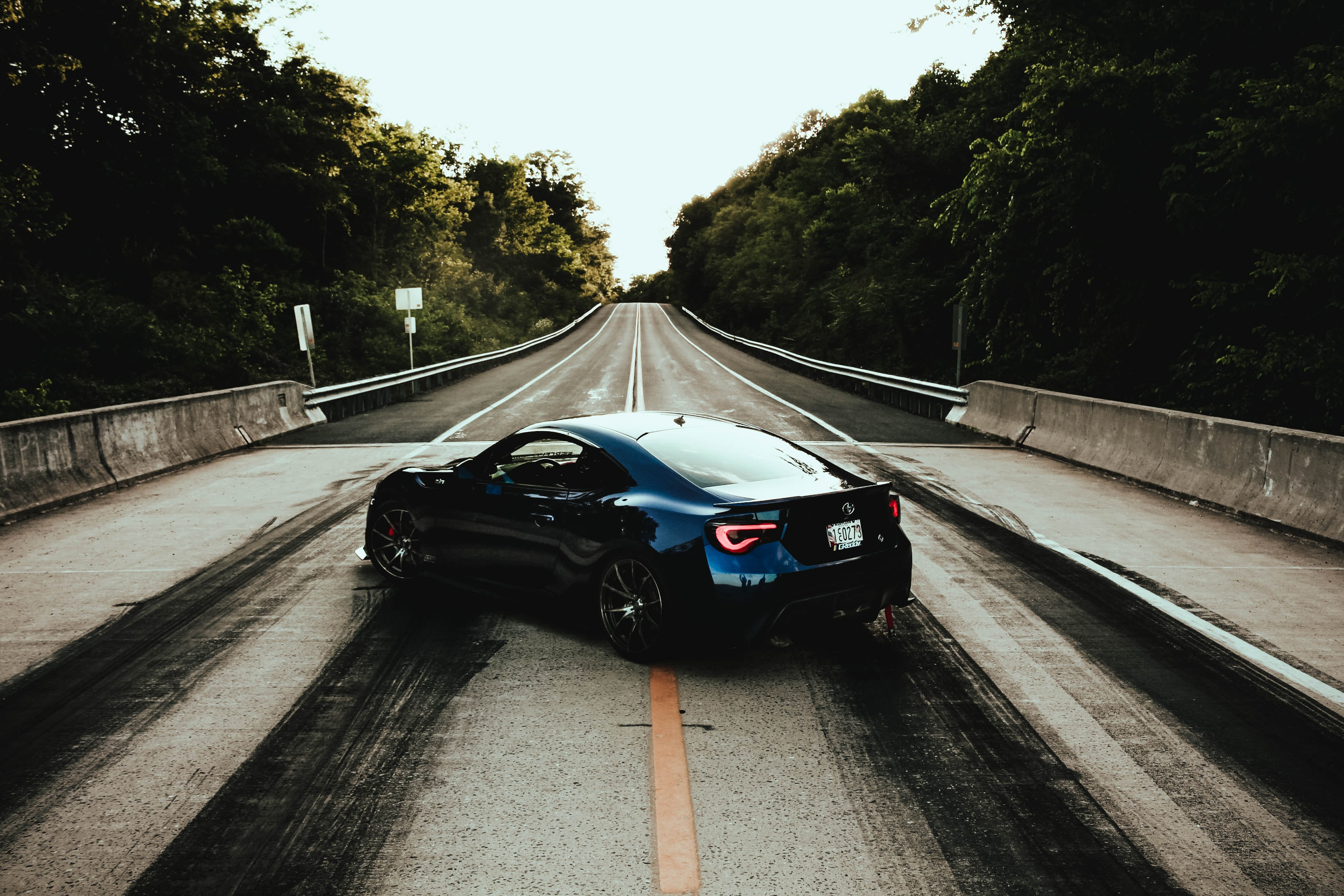 blue coupe of road