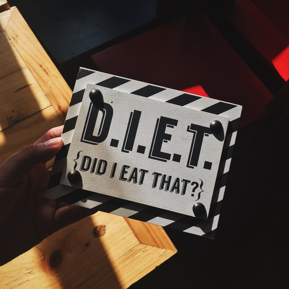 person holding DIET quote board