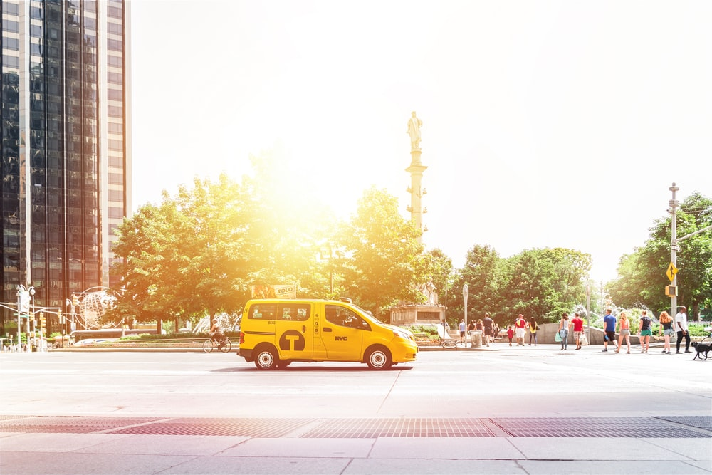 photo of yellow compact van during daytime