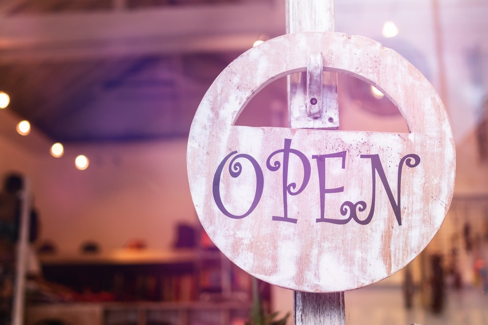 selective focus photography of store open sign hanging on door
