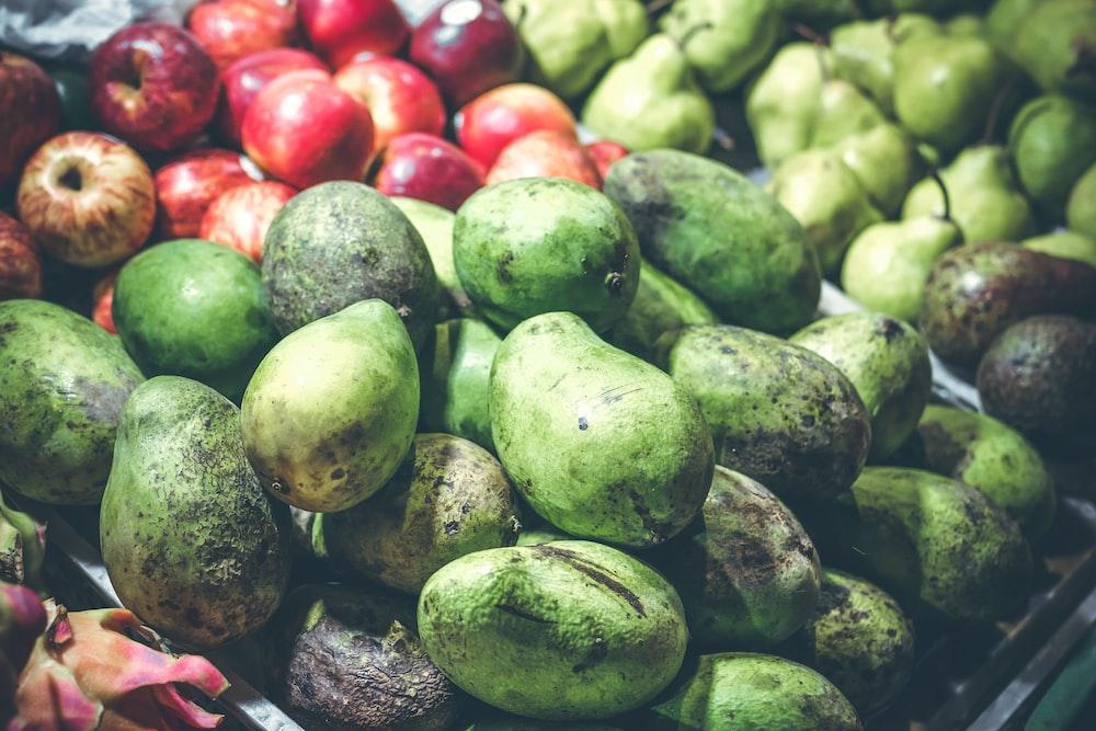 green mango fruits near apple fruits