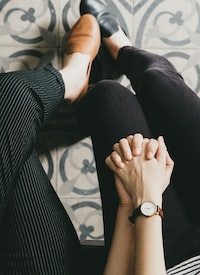 man and woman holding hands while sitting on chair