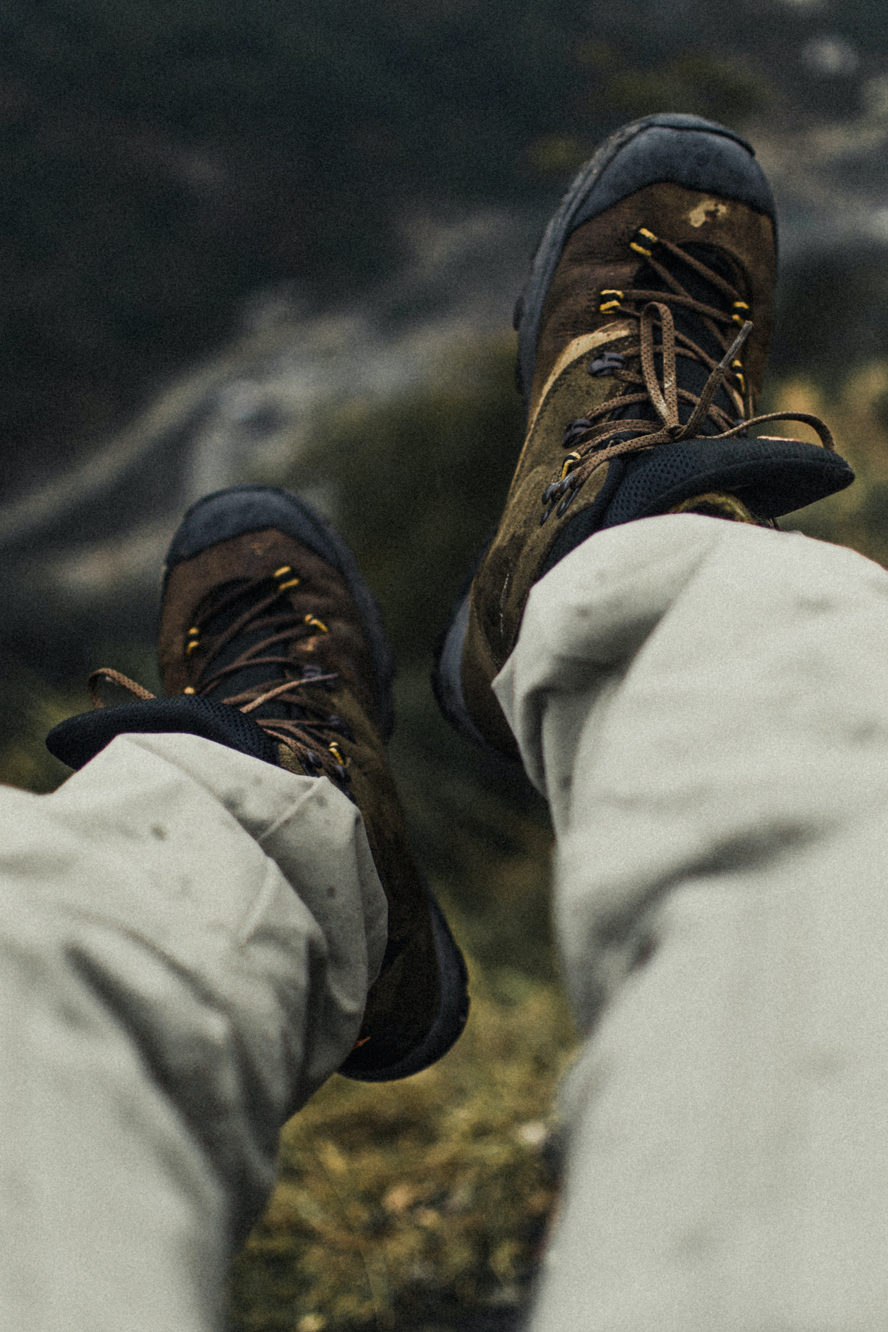 selective focus photography of person wearing hiking shoes