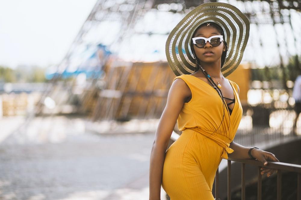 tilt shift lens photography of women's wearing yellow sleeveless top