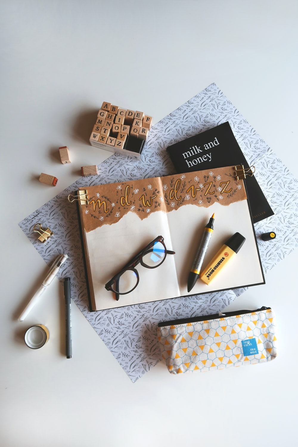 book, marker pen, and eyeglasses on white surface