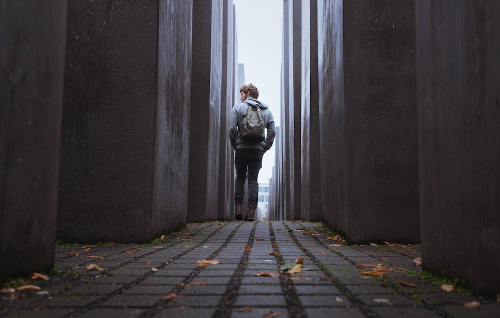 man walking through gray walls