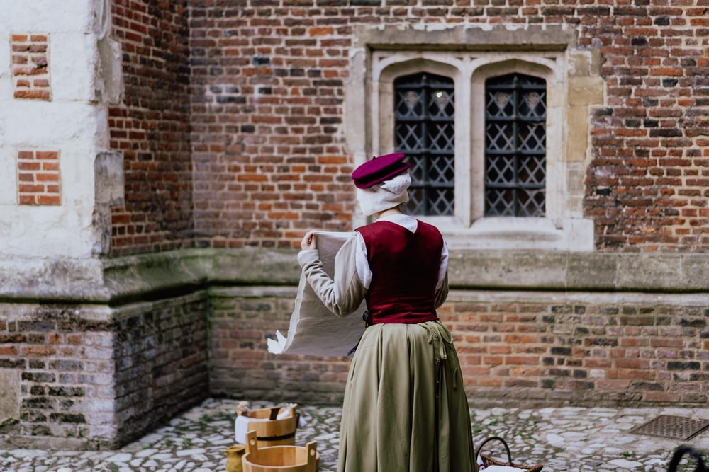 woman doing laundry outside with brown buckets