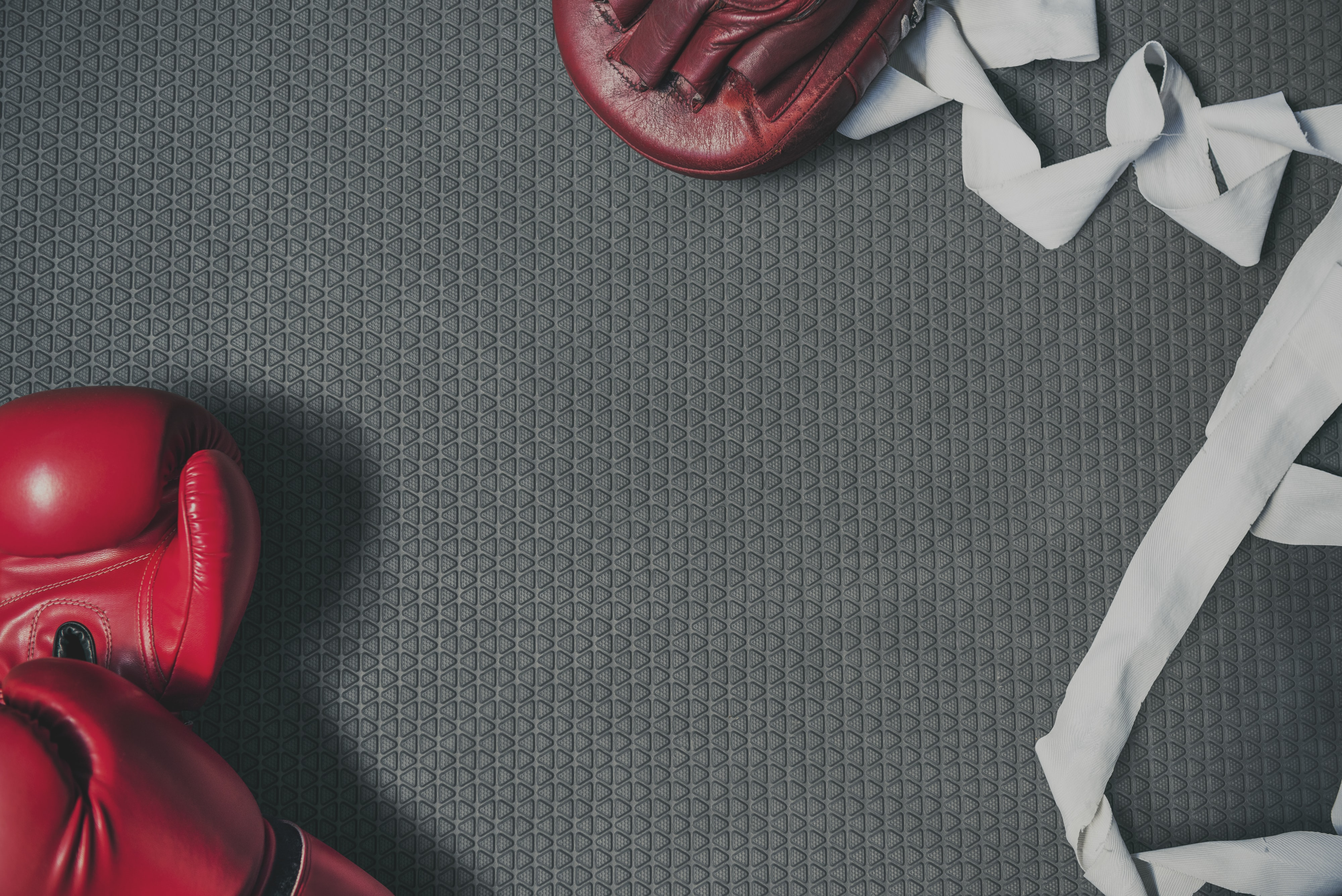 two red boxing gloves on grey surface