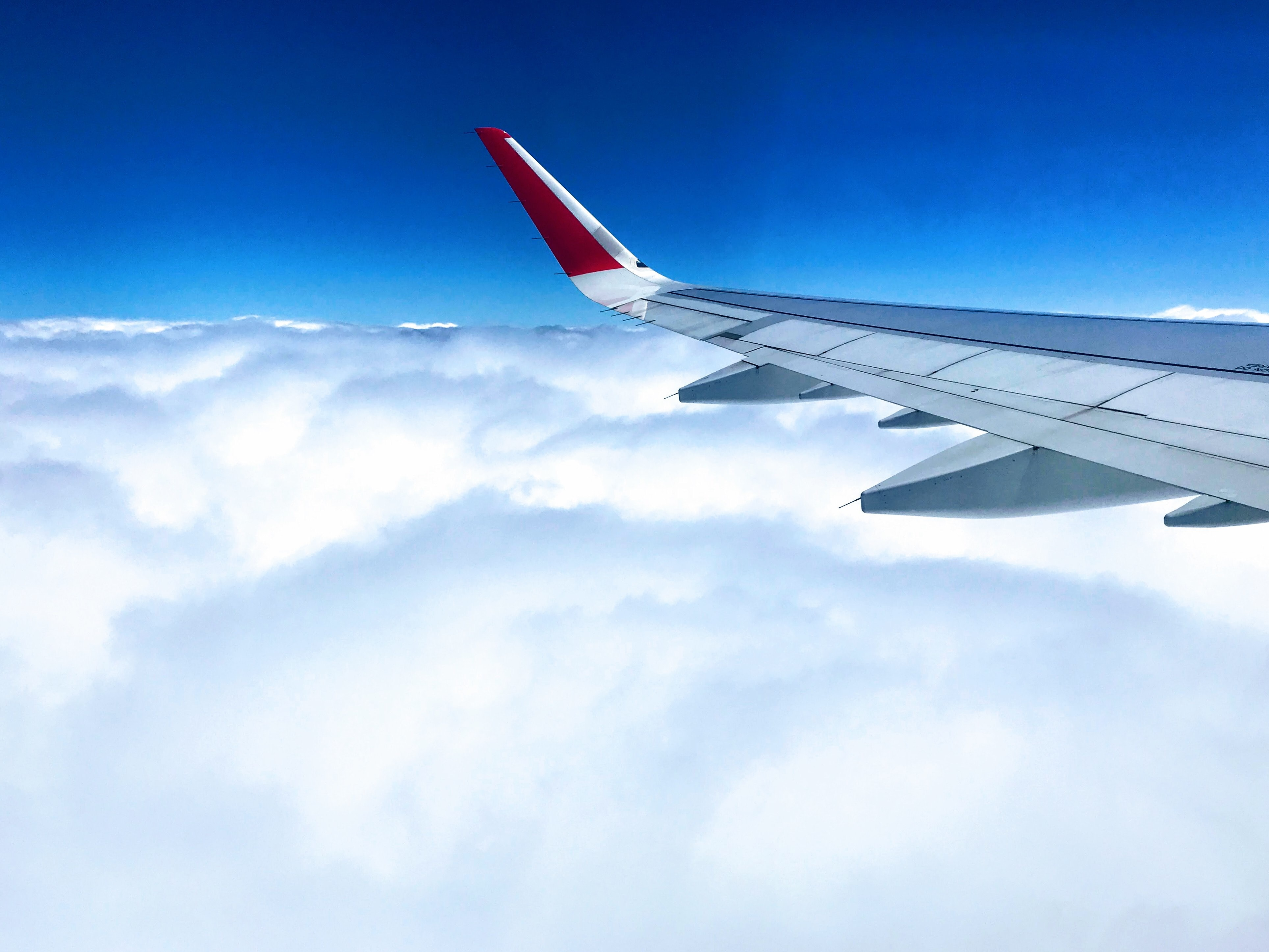 white and red airplane wing above cloudy skies