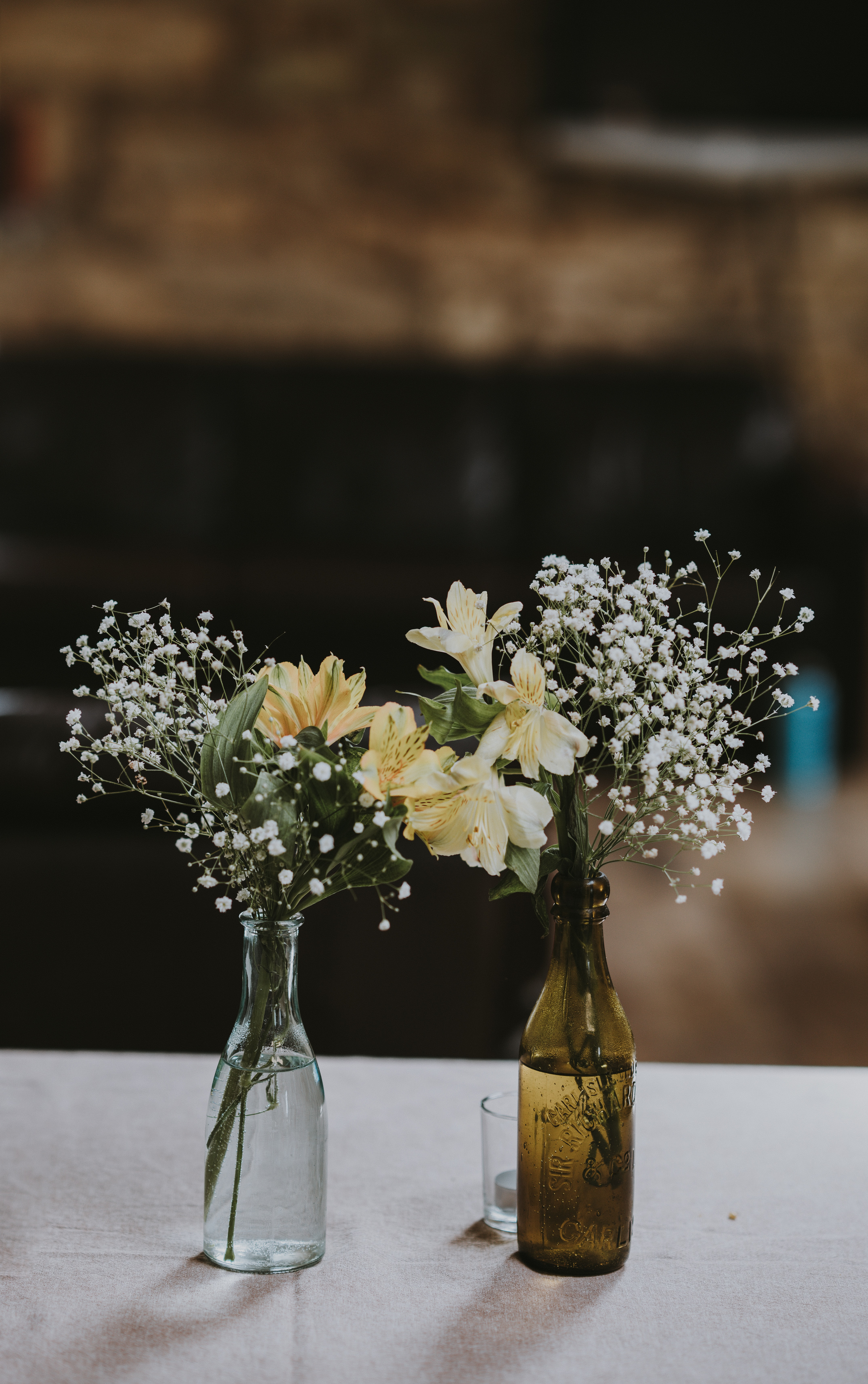 white and yellow flowers on clear glass bottles