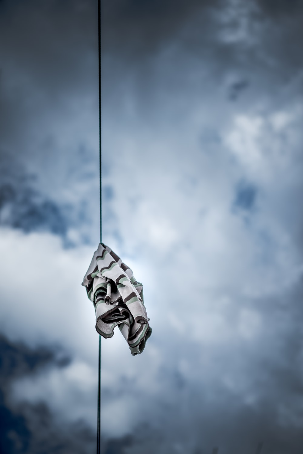 black and gray striped textile hanged from black cable during cloudy day