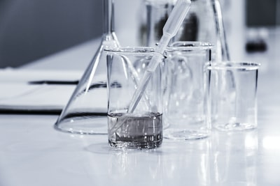three clear beakers placed on tabletop science teams background