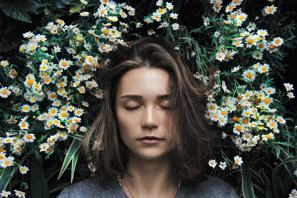 woman closing her eyes on white flower