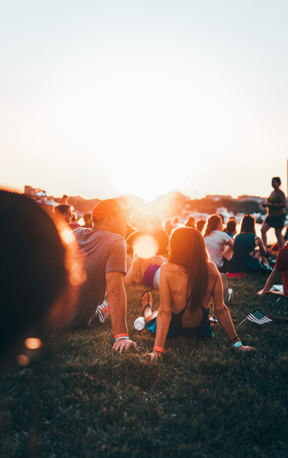 man and woman sitting on grass surrounded with people during golden hour
