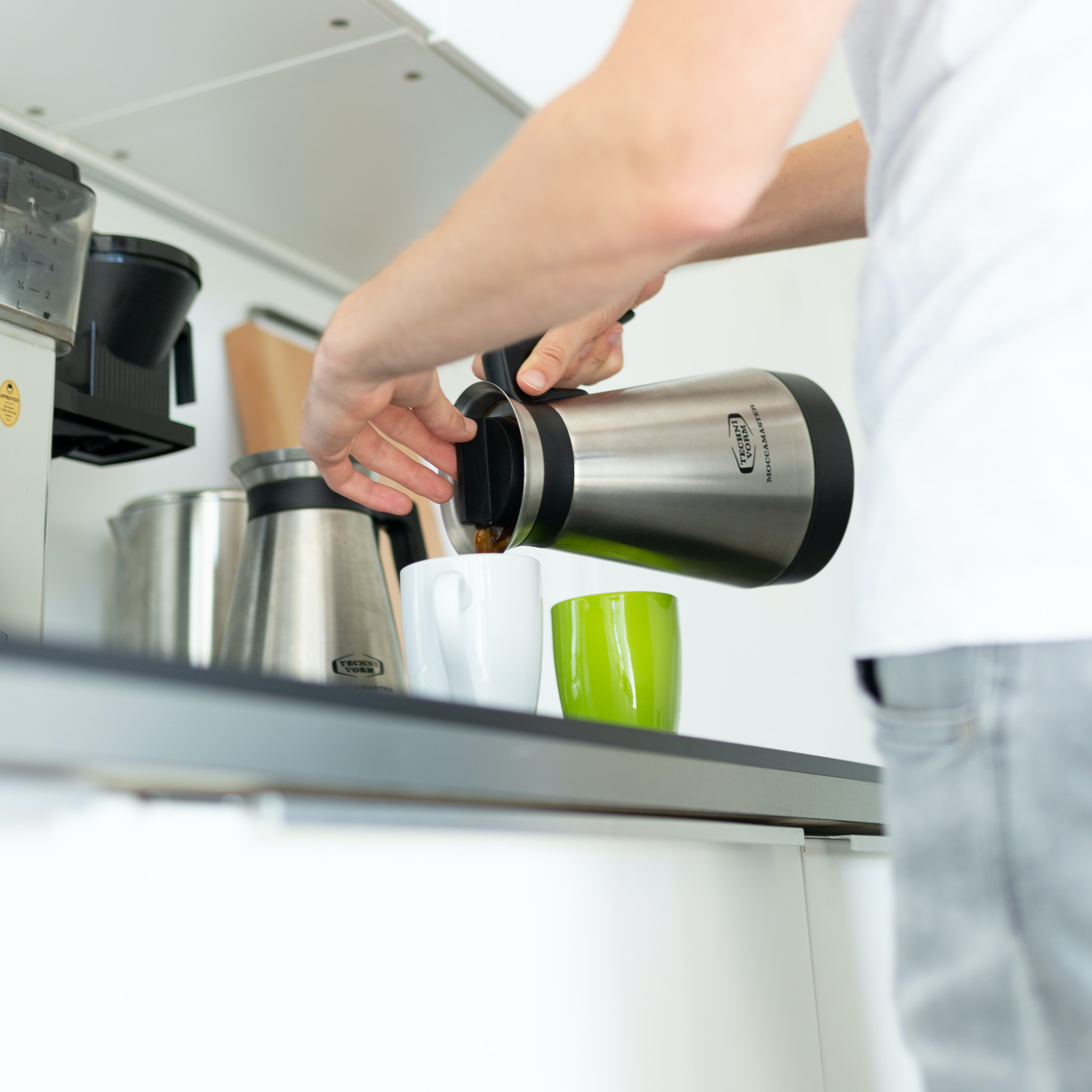 person holding kettle pouring coffee into cup