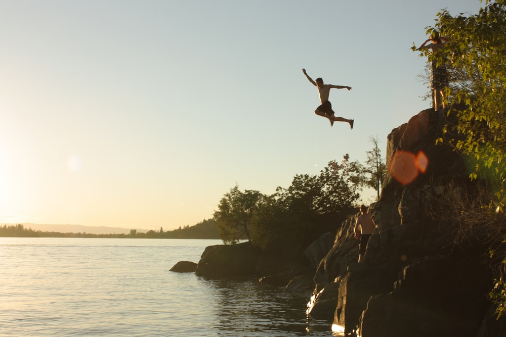 person diving from cliff to body of water during sunset