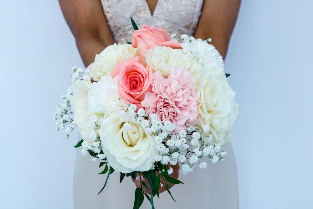 woman wearing white sleeveless wedding dress holding flower bouquet