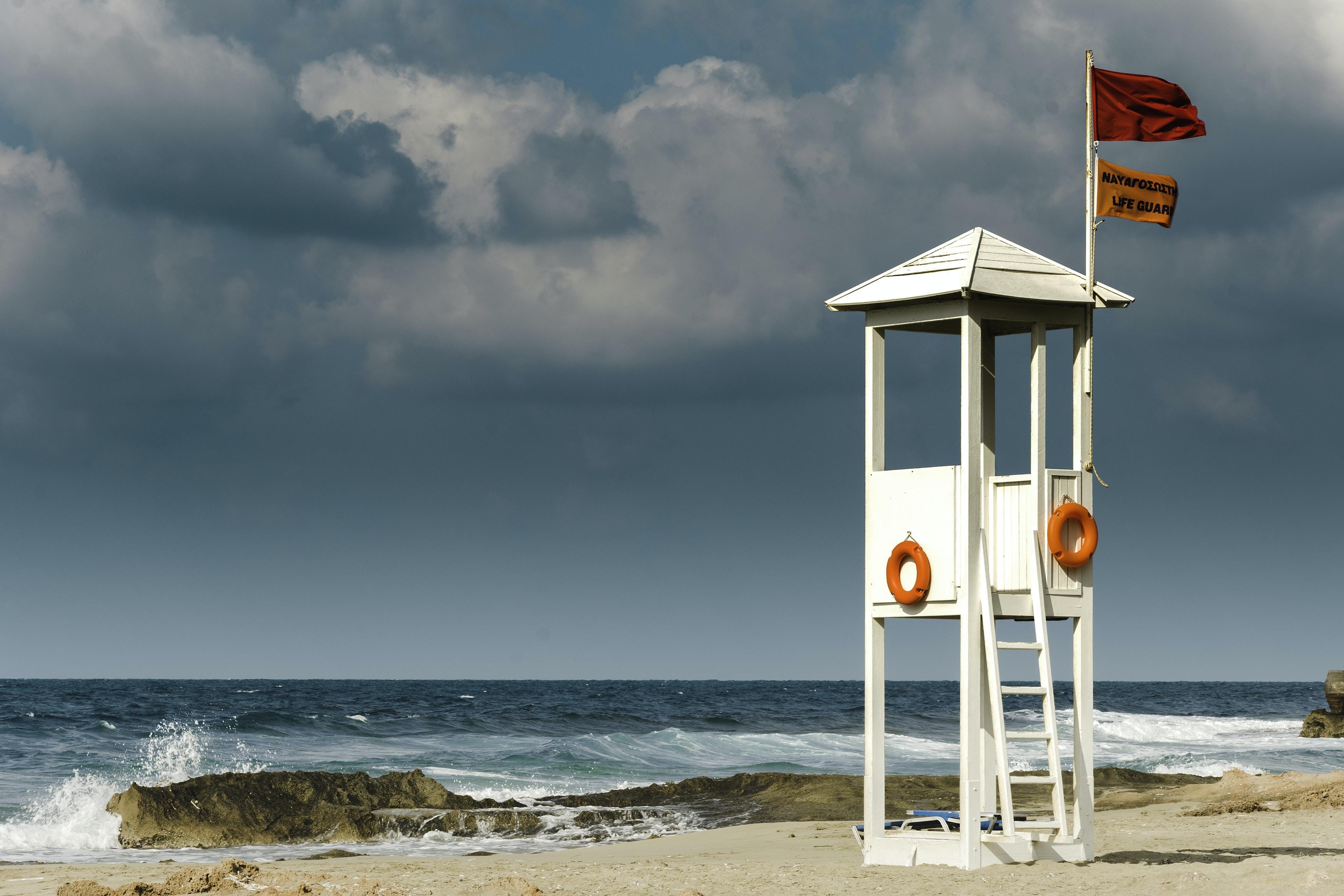 white wooden lifeguard house near seashore