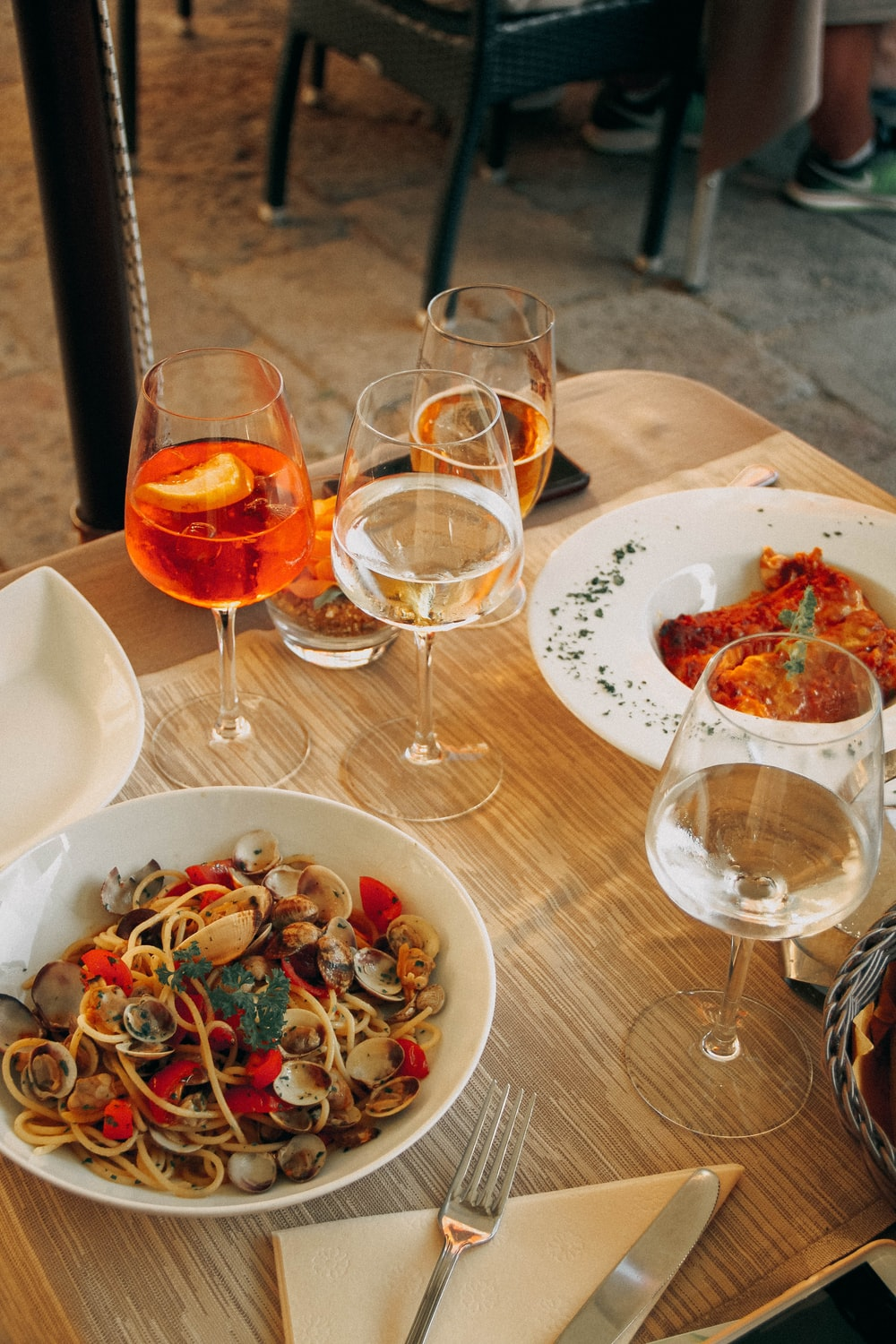 four filled wine glasses and foods on table