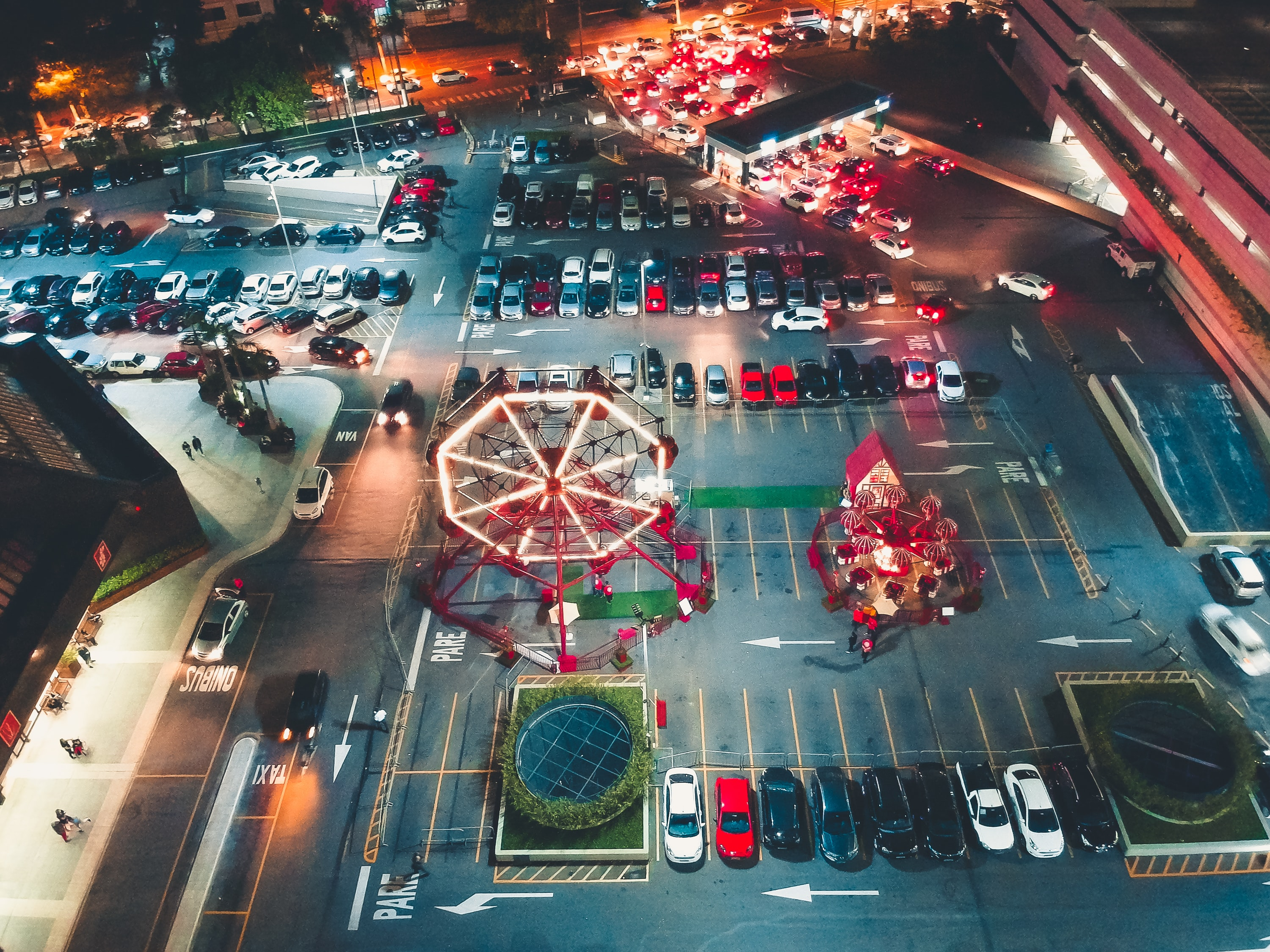 aerial photography of parking lot full of vehicles and carnival rides