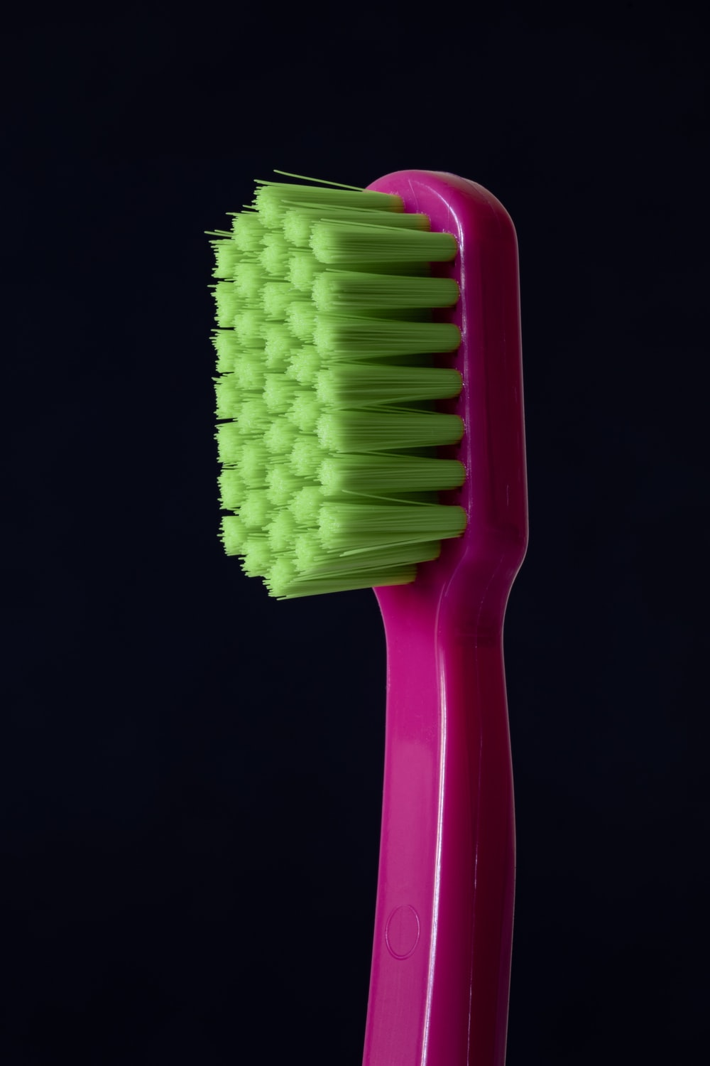 closeup photo of purple and green toothbrush