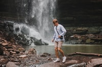 man standing beside river and waterfalls