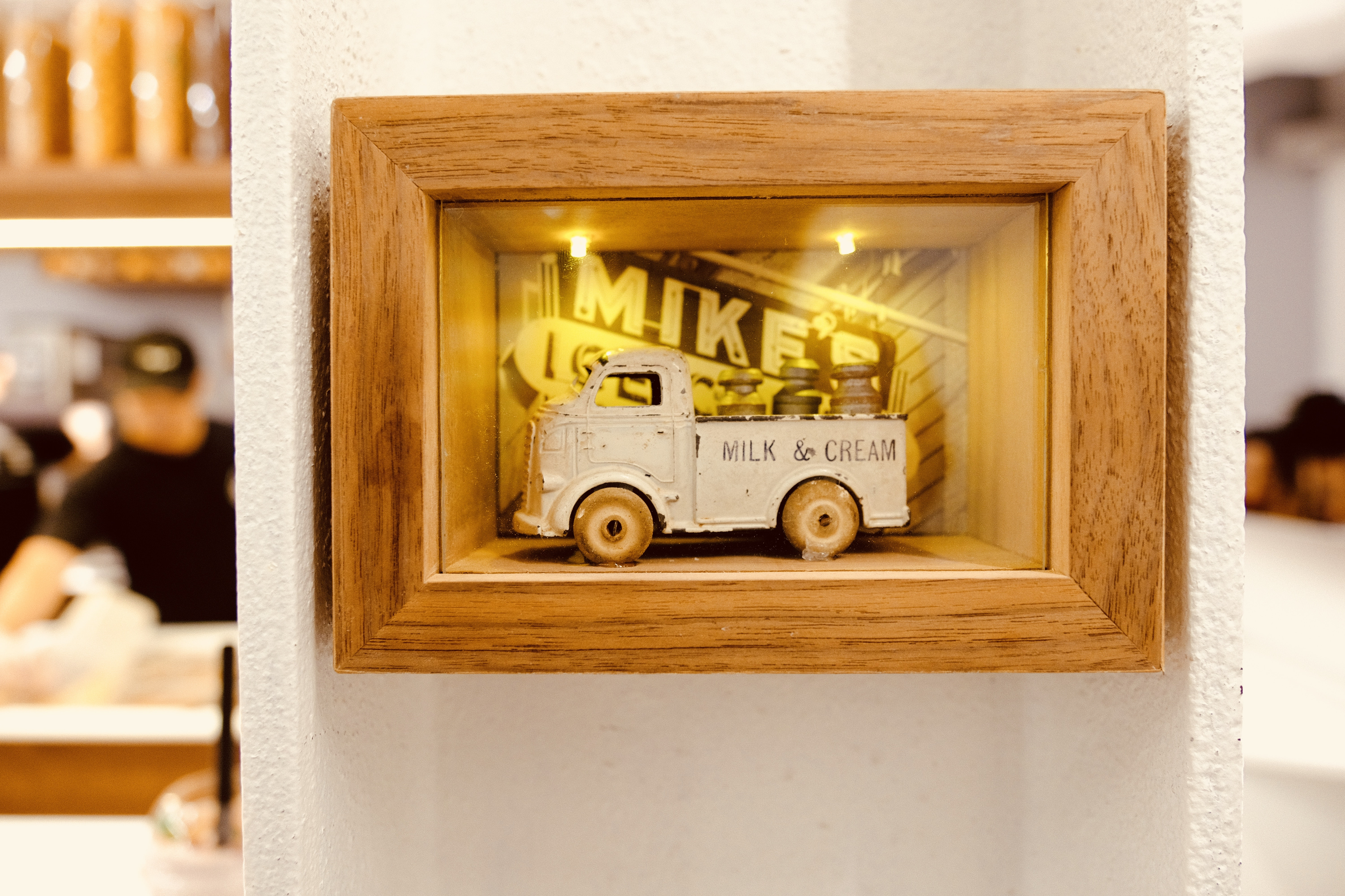 gray truck toy with brown wooden frame on wall
