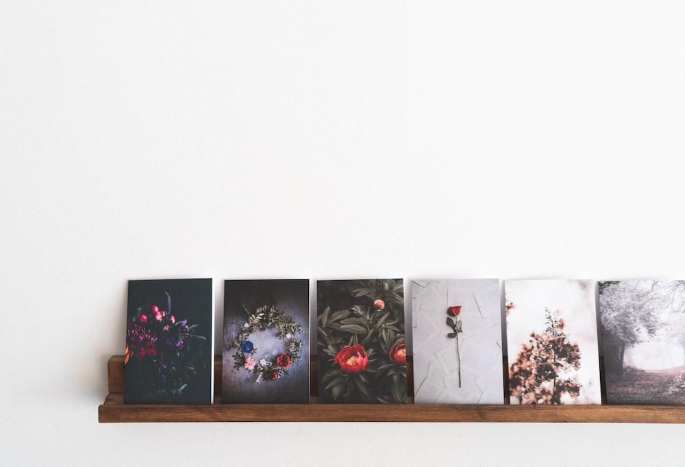 several paintings on brown wooden rack