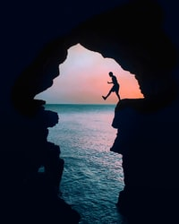 silhouette photography of a man on cliff