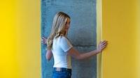 woman wearing white shirt holding yellow painted wall