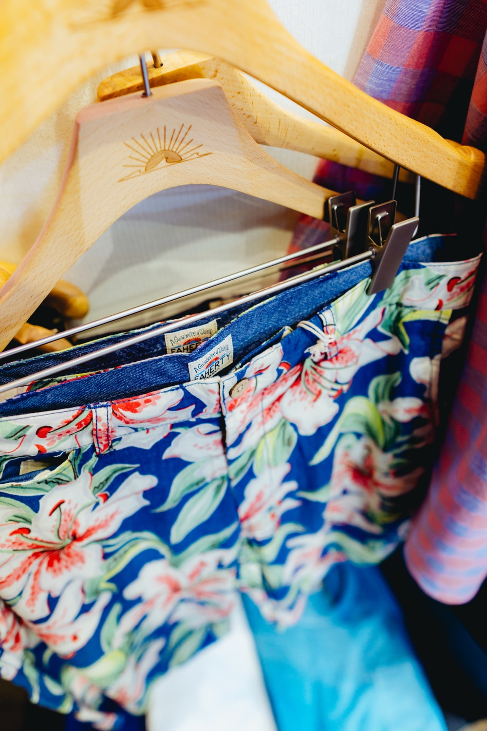 person holding blue and pink floral shorts