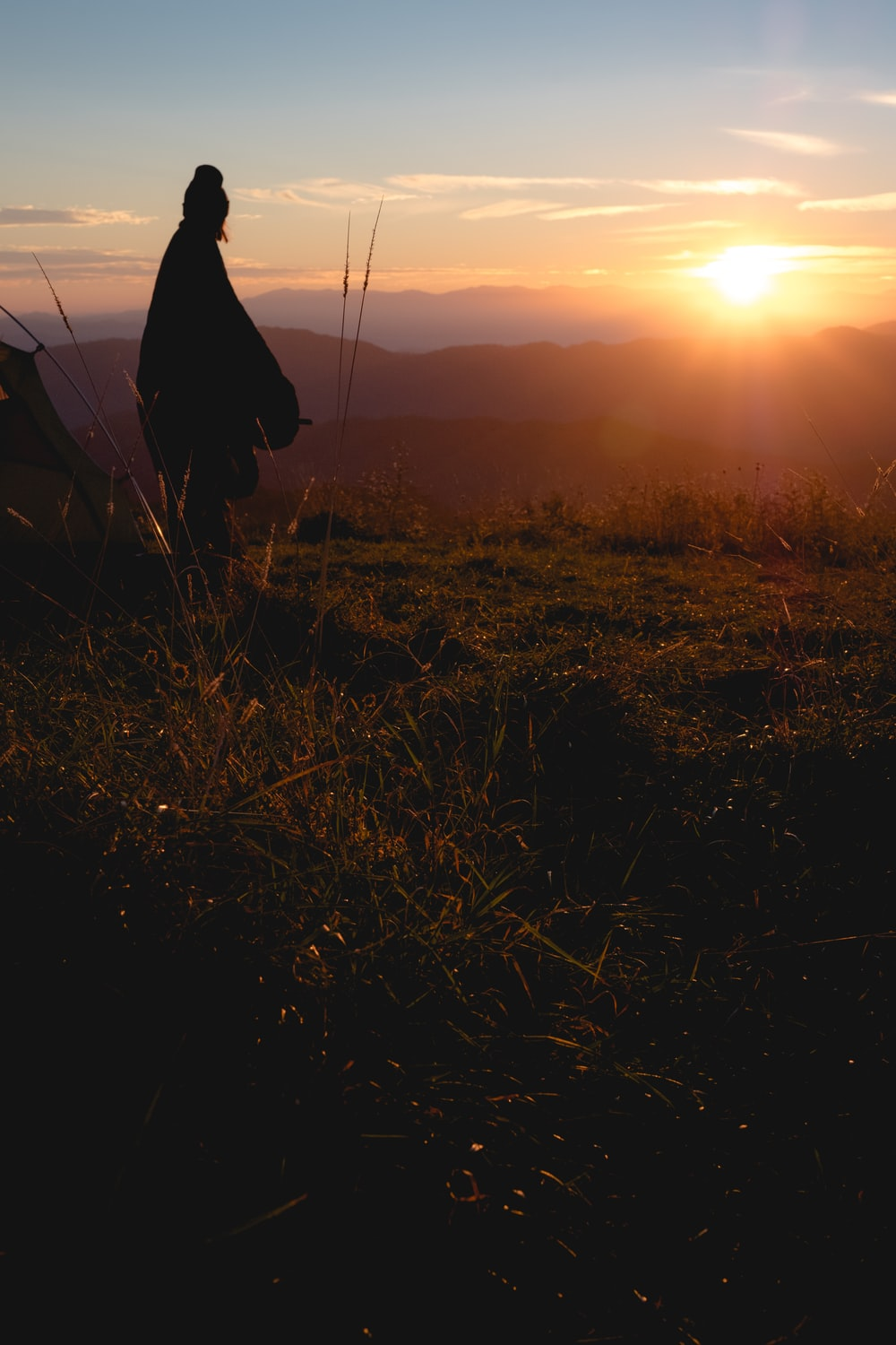 silhouette photo of person wearing robe standing on hill