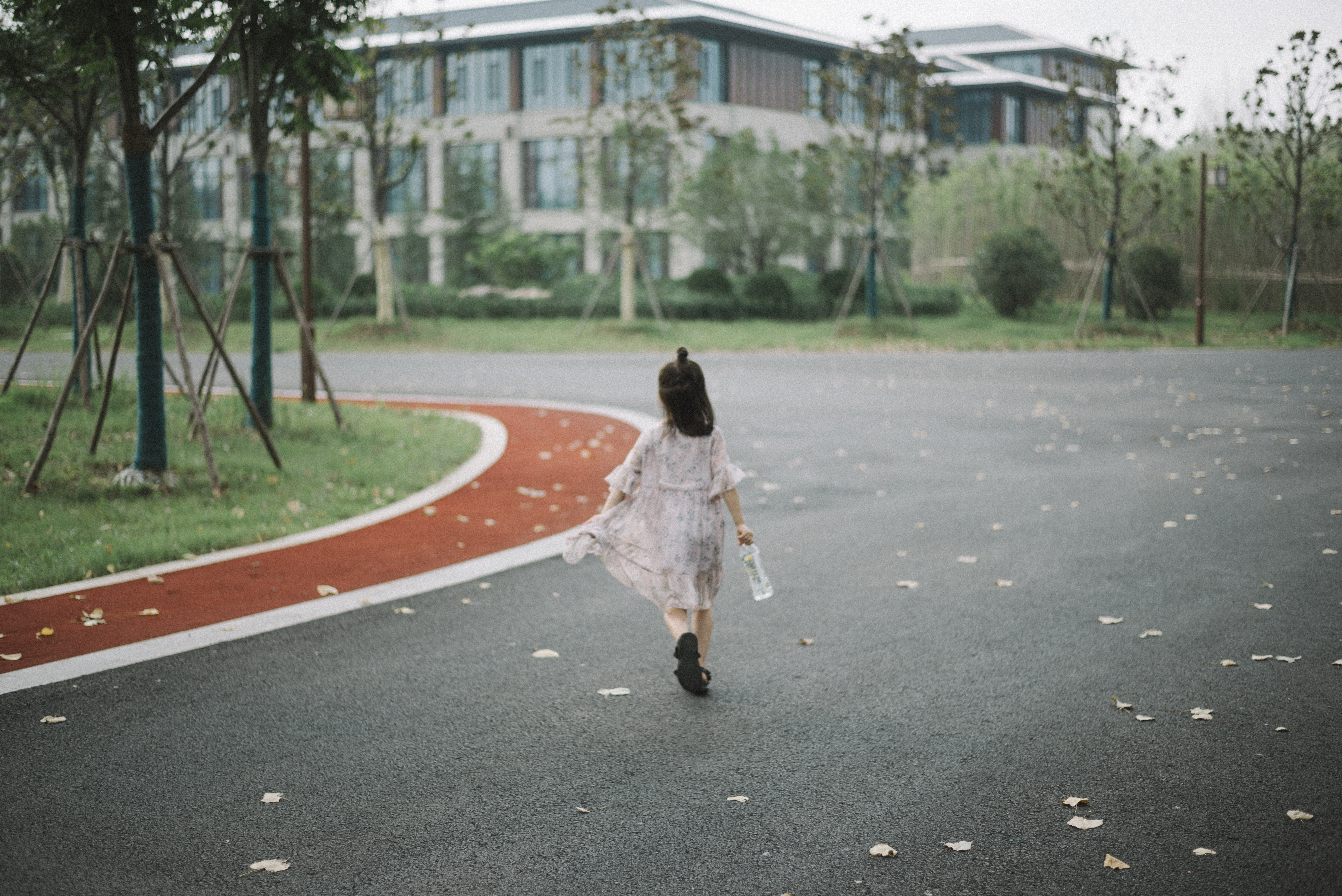 girl holding clear plastic bottle walking on road