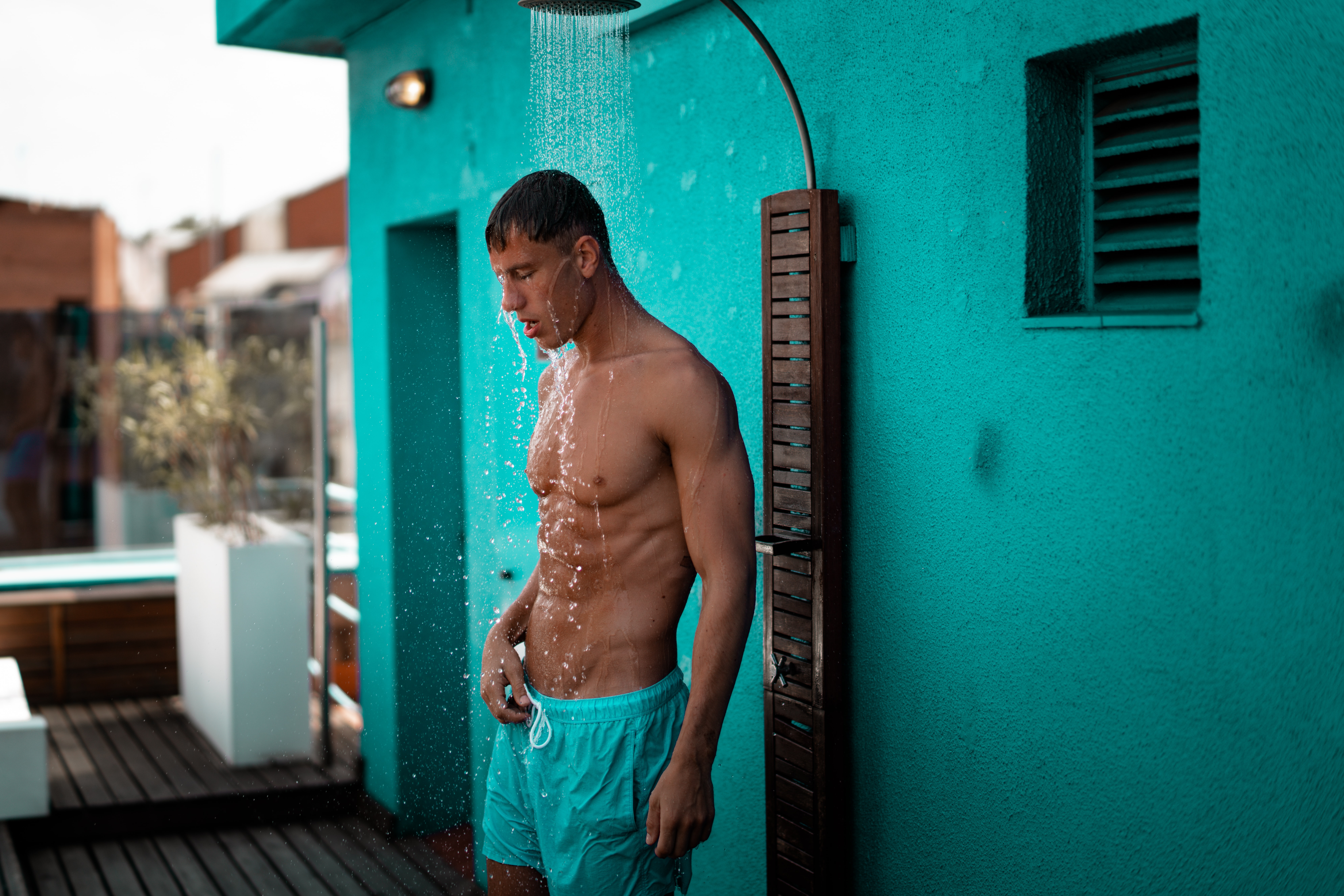 man in teal drawstring shorts taking a shower