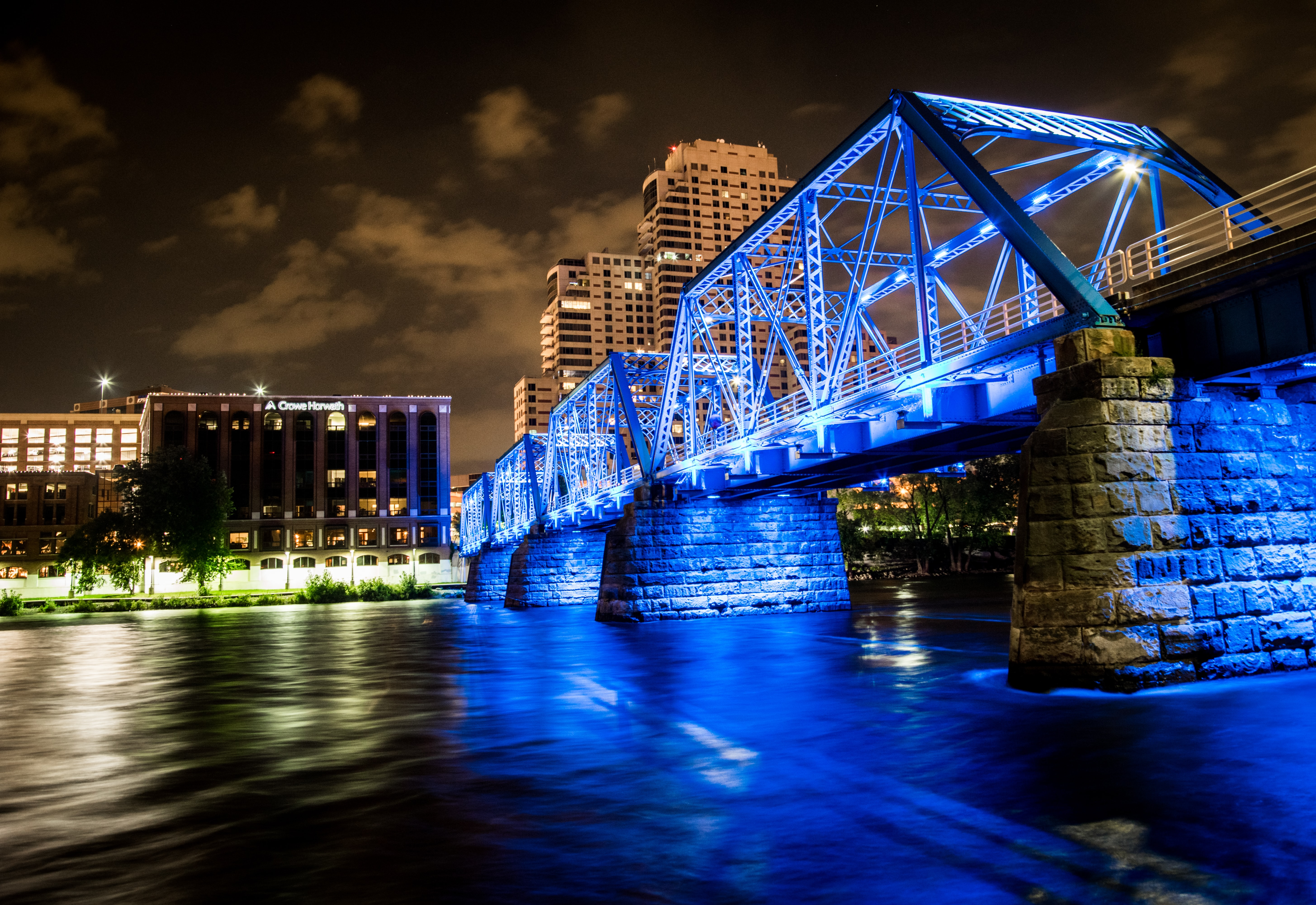 bridge over body of water leading to buildings during nighttime