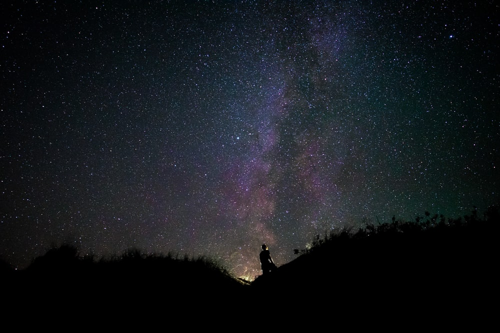silhouette of man on mountain during nighttime
