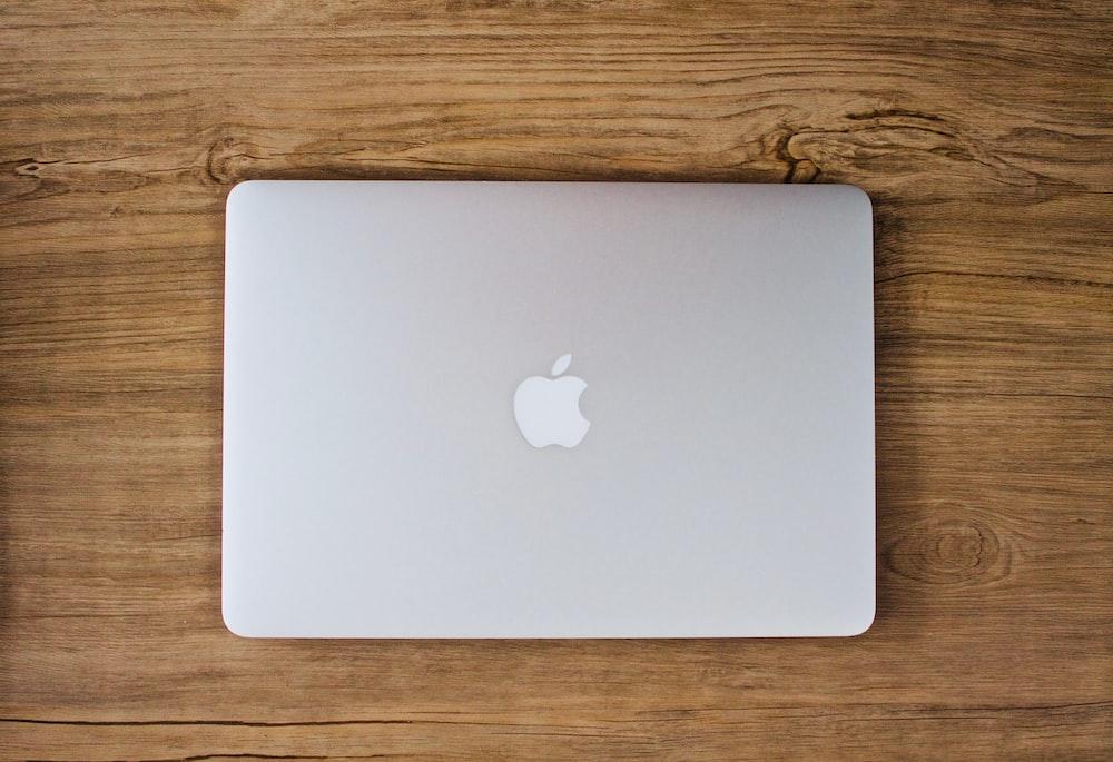 テーブルの上の銀のMacBookの写真を撮る人