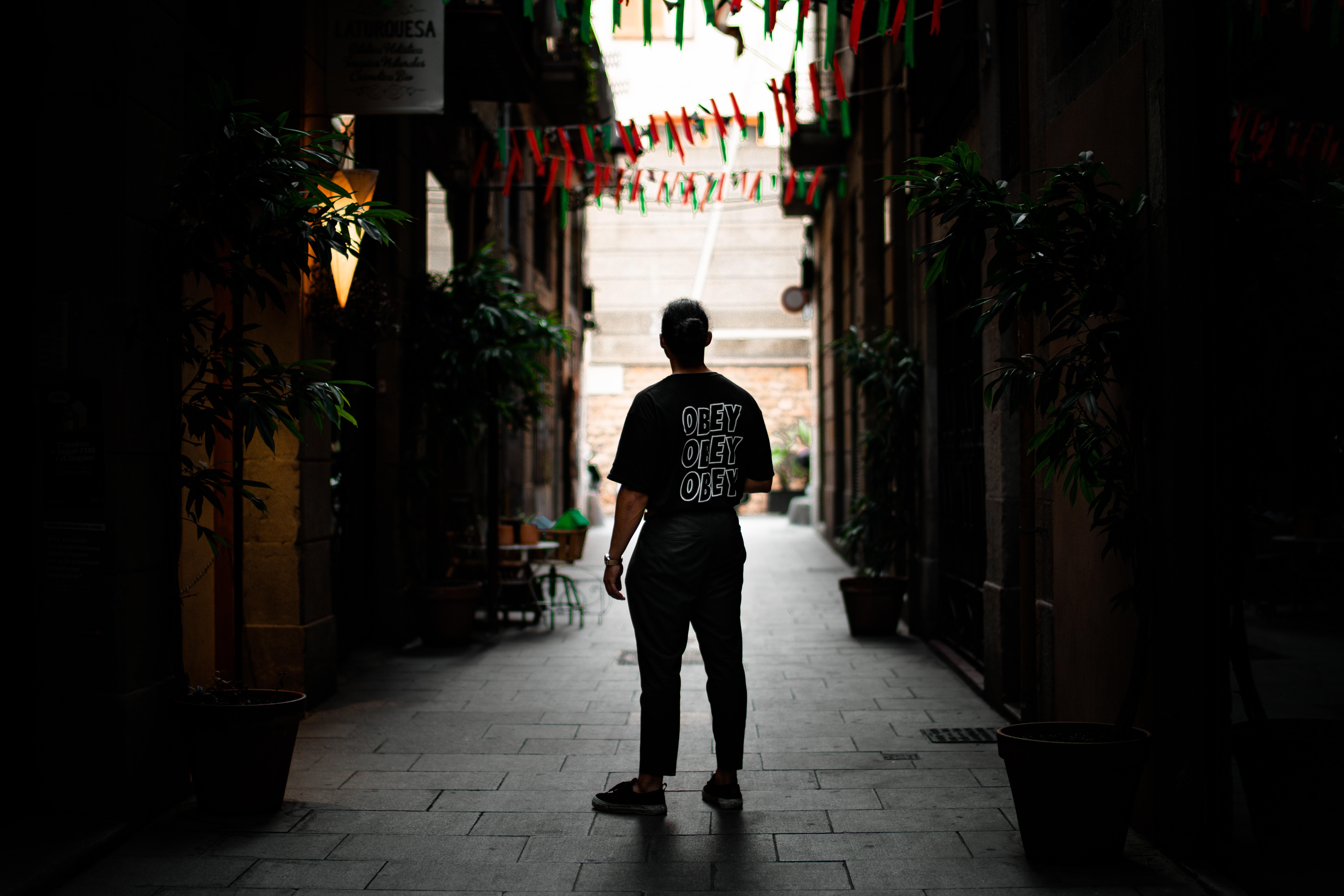 man standing in alley between buildings