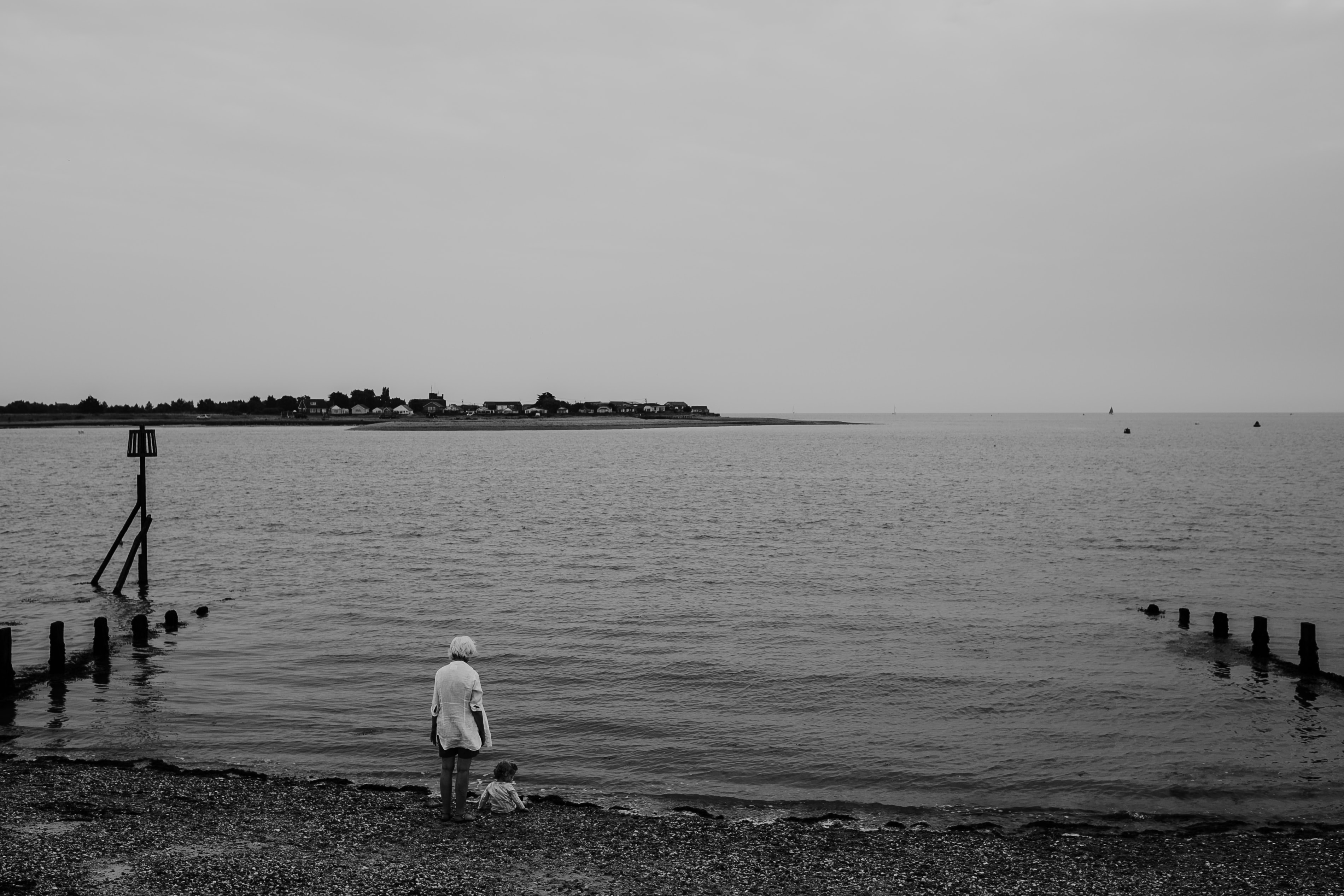 grayscale photo of woman and toddler near body of water