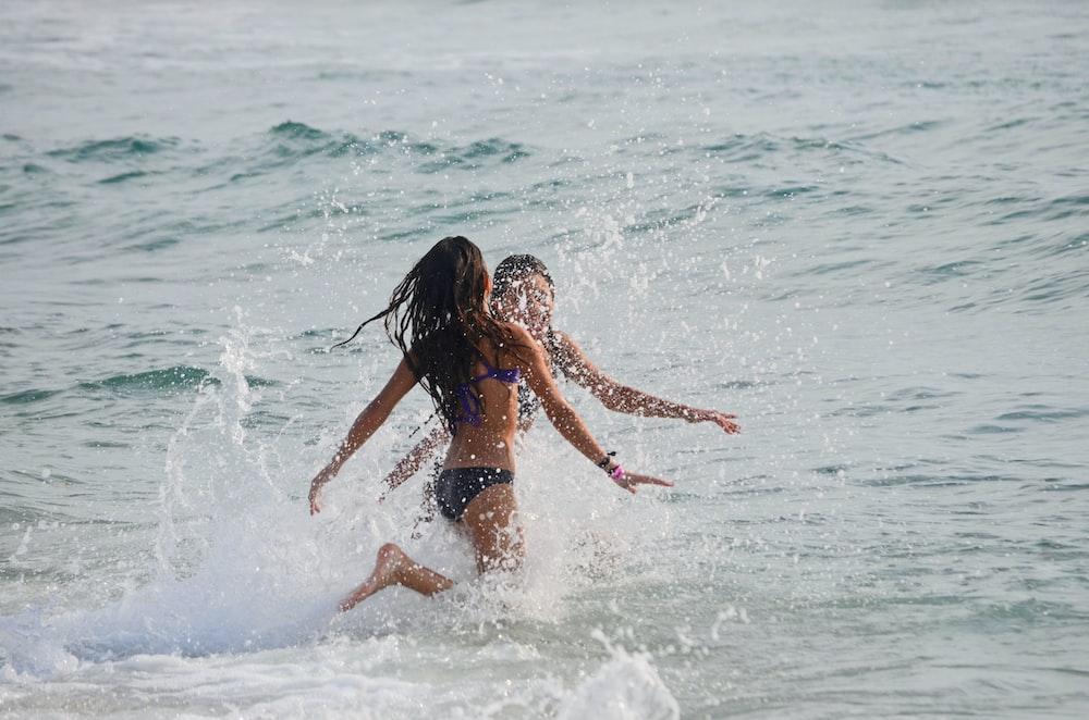 two women walking on body of water