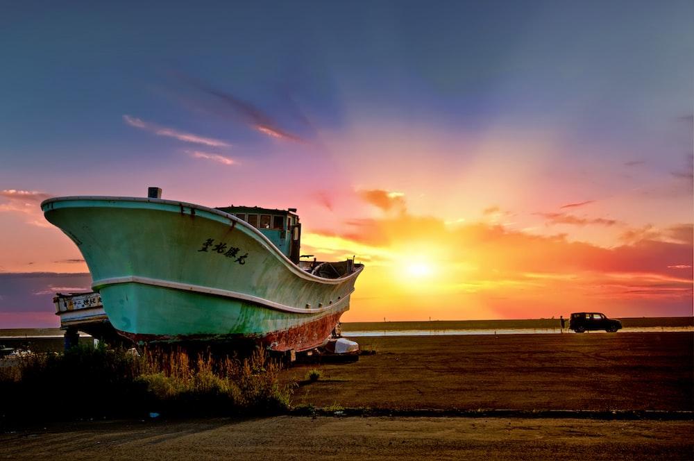 green ship on seashore during golden hour