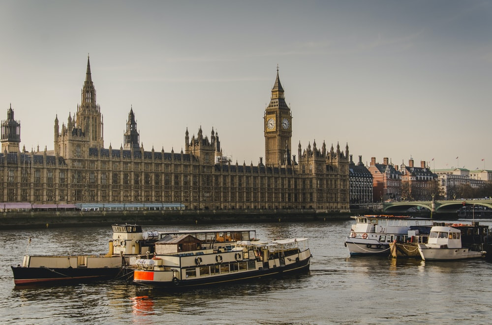 four white boats traveling on river beside Big Ben in London
