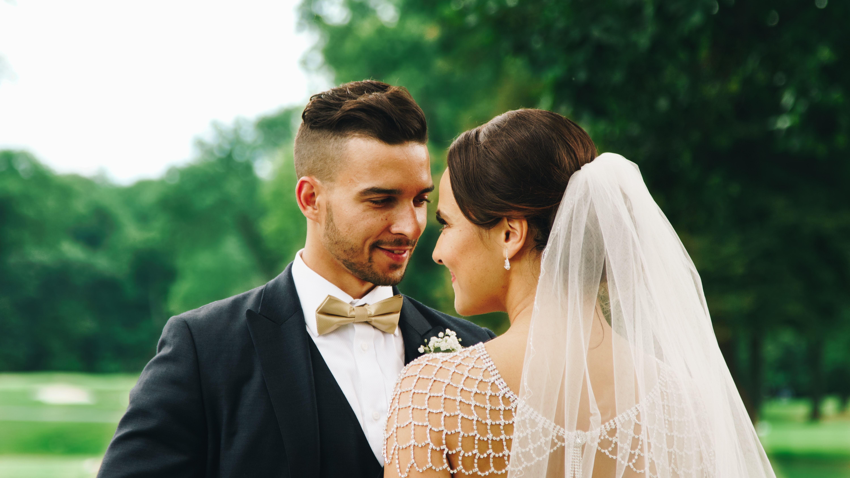 bride and groom near trees under gray sky